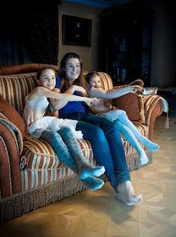 Zdjęcie rodziny z dziećmi oglądającymi telewizję późnym wieczorem