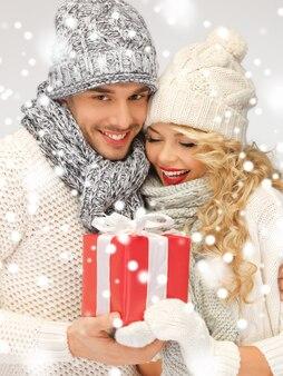 Zdjęcie romantycznej pary w sweterkach z prezentowym pudełkiem