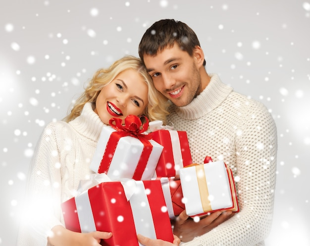 Zdjęcie romantycznej pary w swetrach z pudełkami na prezenty