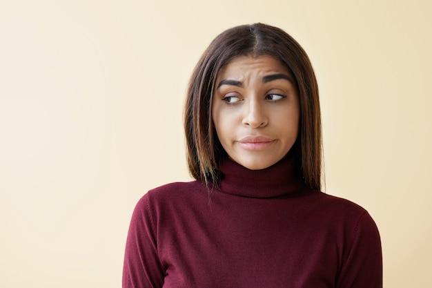 Zdjęcie rozczarowanej młodej brunetki o ciemnej karnacji patrzącej na boki z oczami wyrażającymi smutek i rozczarowanie, zdenerwowaną podczas stresu w pracy lub problemów w życiu osobistym