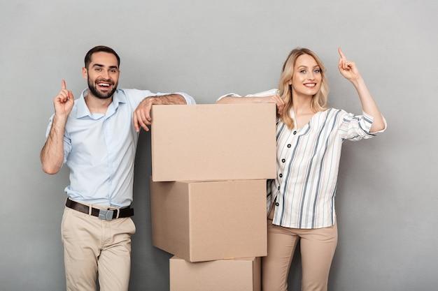 Zdjęcie roześmianej pary w swobodnym ubraniu, stojącej w pobliżu kartonów i wskazującej palce w górę na białym tle