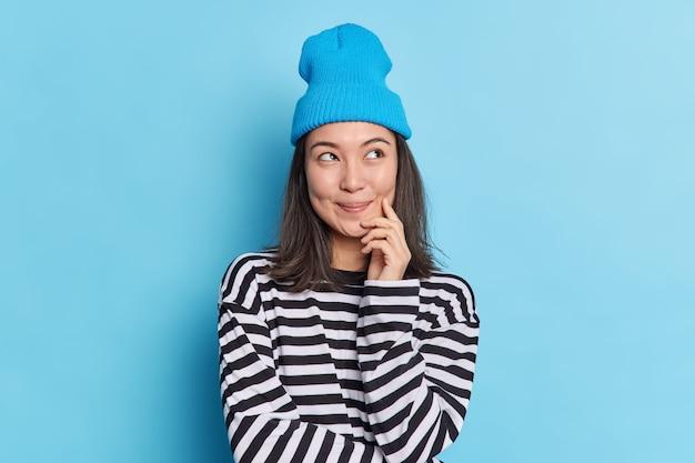 Zdjęcie rozmarzonej azjatki skoncentrowanej na górze z zadowolonym wyrazem twarzy trzymającej rękę na brodzie wyobraża sobie coś przyjemnego w myślach głęboko zastanawia się nad wyborem nosi stylowe ubrania