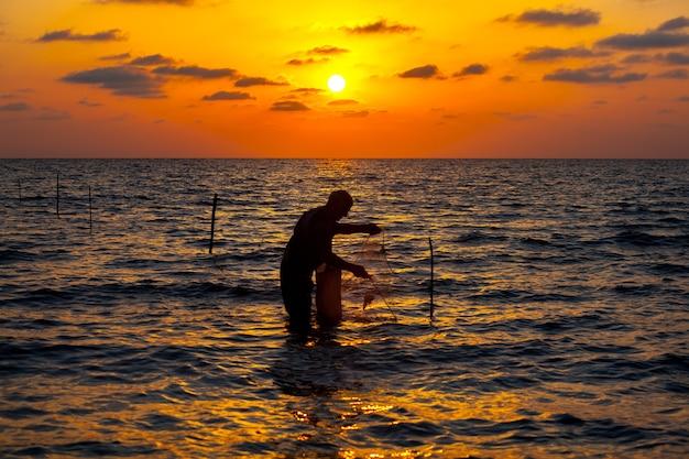 Zdjęcie rybaka używającego sieci do łowienia ryb podczas zachodu słońca, poti, georgia. krajobraz