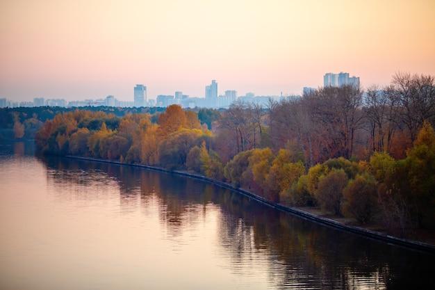 Zdjęcie rzeki, drzew, miasta wieczorem.