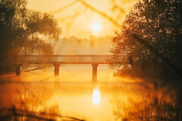 Zdjęcie rzeki, mostu o wschodzie słońca