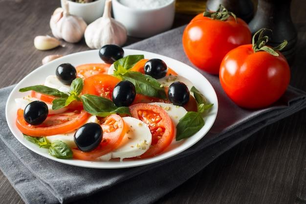 Zdjęcie sałatki caprese z pomidorami, bazylią, mozzarellą, oliwkami i oliwą z oliwek. włoskie tradycyjne składniki sałatki caprese. koncepcja śródziemnomorskiej, ekologicznej i naturalnej żywności.