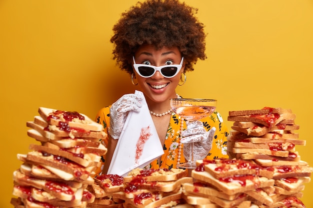 Zdjęcie schludnej i dobrze ubranej ciemnoskórej kobiety, pozuje z kieliszkiem koktajlowym i serwetką, nosi stylowe ubrania, spędza wolny czas w luksusowej restauracji, na pierwszym planie pyszne tosty z dżemem