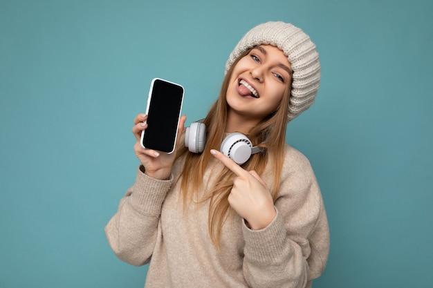 Zdjęcie seksownej atrakcyjnej pozytywnej radosnej młodej ciemnej blondynki ubranej w beżowy stylowy sweter i