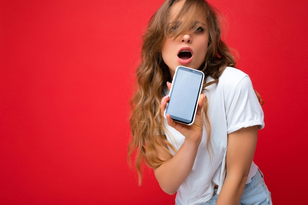 Zdjęcie seksownej zdziwionej młodej blondynki dobrze wyglądającej noszącej białą koszulkę stojącą na białym tle na czerwonym tle z kopią przestrzeni trzymającej telefon pokazujący smartfon w ręku z pustym ekranem dla