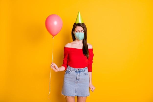 Zdjęcie sfrustrowana dziewczyna w masce medycznej świętować epidemię covid rocznicę dostać otrzymać prezent balon zdenerwowany weat czerwony top dżinsy spódnica na białym tle jasny połysk kolor tła