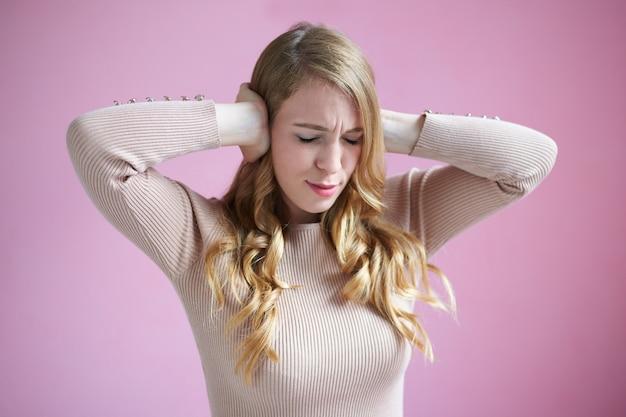Zdjęcie sfrustrowanej pięknej młodej kobiety rasy kaukaskiej z długimi blond falującymi włosami zakrywającymi uszy, nie może znieść głośnych dźwięków z powodu strasznego bólu głowy lub migreny