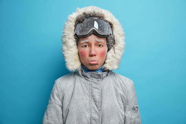 Zdjęcie sfrustrowanej zamarzniętej kobiety z szarą twarzą pokrytą szronem spędza czas na świeżym powietrzu w mroźny zimowy dzień, nosi okulary snowboardowe i ciepłą kurtkę termo.