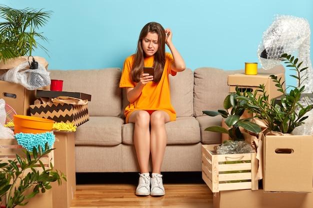 Zdjęcie sfrustrowanej zdziwionej kobiety drapie się po głowie patrząc na smartfona, próbuje zapłacić za mieszkanie w aplikacji online, zmienia mieszkanie