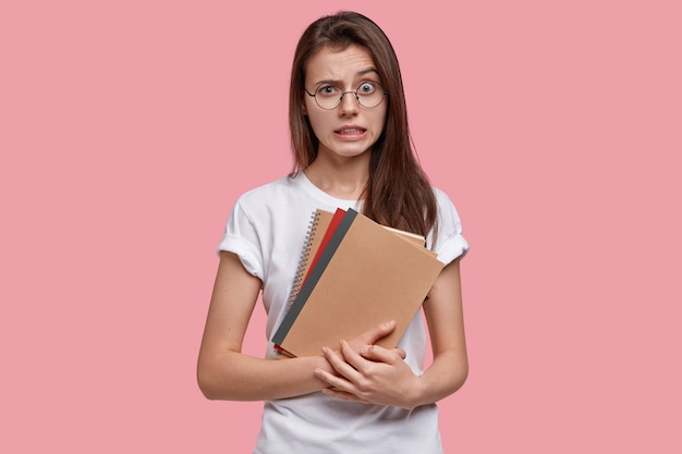 Zdjęcie sfrustrowanej, zdziwionej młodej kobiety wygląda w oszołomieniu, unosi brwi, ma ciemne włosy, białą swobodną koszulkę