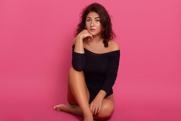 Zdjęcie siedzącej na podłodze delikatnej, wspaniałej atrakcyjnej dziewczyny o świetnym kształcie figury, pozującej odizolowanej na różowej przestrzeni, trzymającej rękę pod brodą. ubrany w czarny kombinezon.