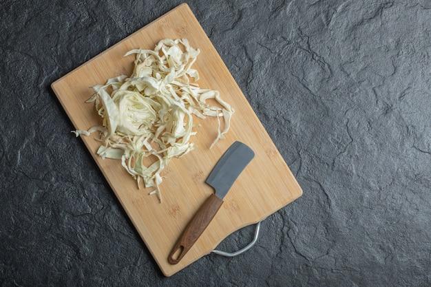Zdjęcie siekanej kapusty i noża na drewnianej desce do krojenia. wysokiej jakości zdjęcie