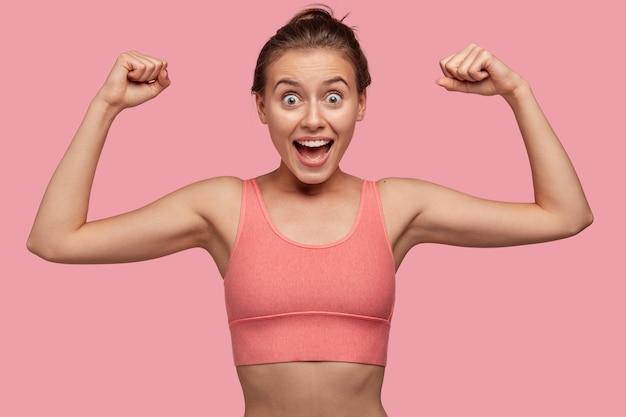 Zdjęcie silnej, wesołej młodej sportsmenki pokazuje, jak biceps działa na mięśnie na siłowni, nosi luźny top w jednym tonie ze ścianą, ma zdrowe, idealne ciało, jest zdumiony. koncepcja sportu