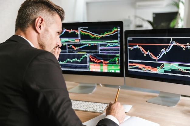 Zdjęcie skoncentrowanego biznesmen 30s na sobie garnitur siedzi przy stole w biurze i pracuje z grafiką i wykresami na komputerze