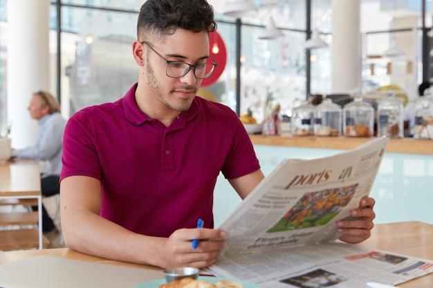 Zdjęcie skoncentrowanego mężczyzny z poważnym wyrazem twarzy, czyta gazetę, dowiaduje się o nowościach ze świata, trzyma długopis, aby podkreślić najważniejsze fakty, nosi okulary i swobodną koszulkę, pozuje nad wnętrzem kawiarni