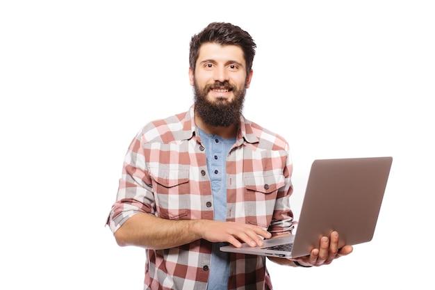 Zdjęcie skoncentrowanego młodego brodatego mężczyzny w okularach ubranych w koszulę za pomocą laptopa na białym tle nad białą ścianą.