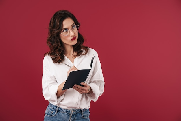 Zdjęcie skoncentrowanego myślenia młoda kobieta w okularach na białym tle na czerwonej ścianie pisania notatek w notesie.