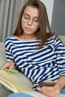 Zdjęcie skoncentrowanej czytelniczki czyta książkę, długopisem podkreśla informacje, stara się wzbogacić swoje słownictwo, trzyma nowoczesny telefon komórkowy, nosi okulary optyczne dla dobrego widzenia, ma poważny wygląd