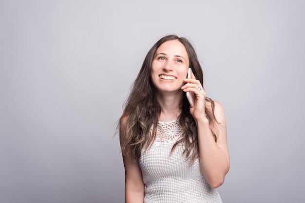 Zdjęcie śliczna młoda kobieta rozmawia na smartfonie z kimś na białej ścianie