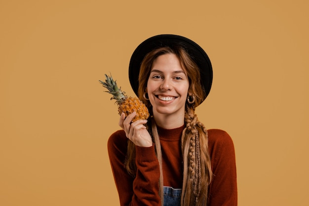 Zdjęcie śliczna rolniczka trzyma ananas z uśmiechem i ładnie wygląda. biała kobieta nosi kombinezon dżinsowy i kapelusz na białym tle w kolorze brązowym.