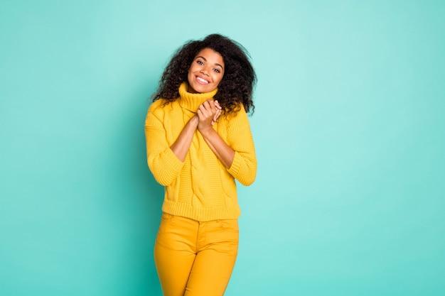 Zdjęcie ślicznej ciemnej skóry, falującej kobiety trzymającej się za ręce razem szczęśliwi wiosenny nastrój nosić żółty sweter z dzianiny stylowe spodnie na białym tle niebieska turkusowa ściana