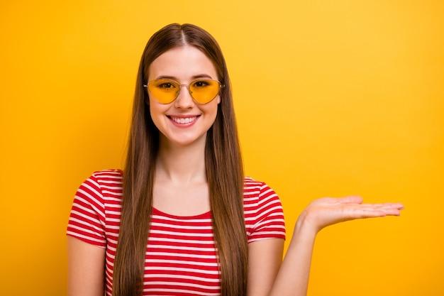 Zdjęcie ślicznej ładnej młodej dziewczyny uśmiechniętej dłoni trzymającej pustą przestrzeń zademonstrować doradzanie polecając produkt nosić specyfikacje przeciwsłoneczne w paski biała czerwona koszula żywy żółty kolor tła