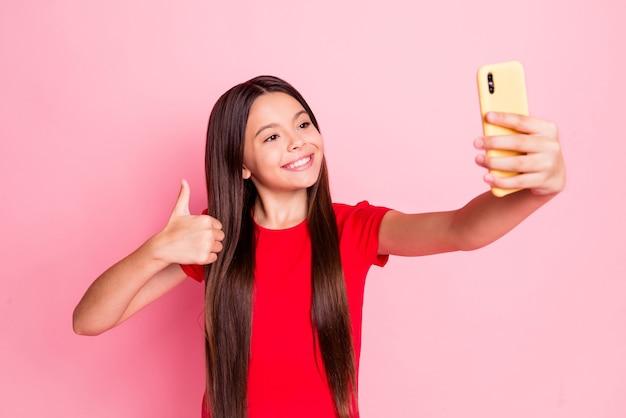 Zdjęcie ślicznej ślicznej małej damy długiej fryzury podnieś rękę przytrzymaj telefon pokaż kciuk-up zrobić selfie ząb promienny uśmiech nosić dorywczo stylowy czerwony t-shirt na białym tle różowy kolor tła