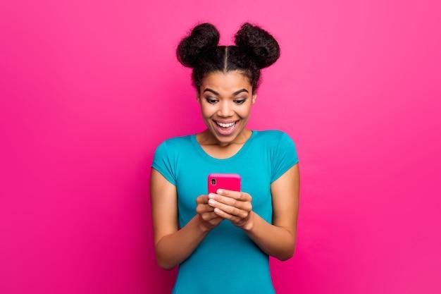 Zdjęcie ślicznej tysiącletniej ciemnoskórej kobiety trzymającej telefon podekscytowany