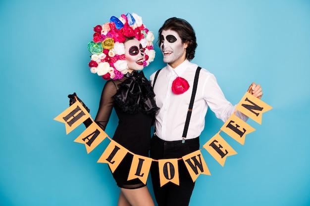 Zdjęcie ślicznej upiornej pary mężczyzna pani przytulić trzymaj oflagowaną wstążkę zademonstrować otwarcie festiwalu nosić czarny krótki mini sukienka śmierć kostium róże opaska na głowę pończoch na białym tle niebieski kolor tła
