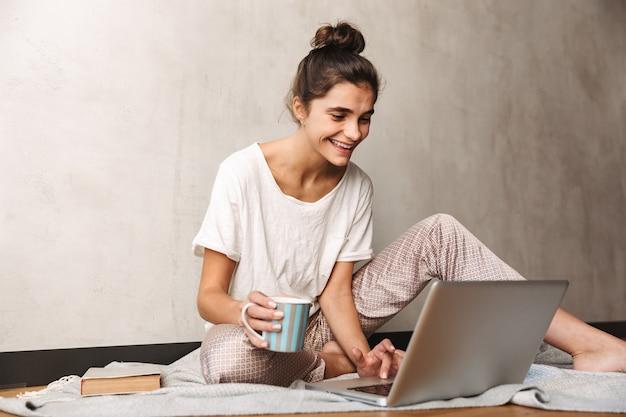 Zdjęcie ślicznej uśmiechniętej kobiety noszącej ubrania rekreacyjne, pijącej kawę i piszącej na laptopie, siedząc na podłodze w domu