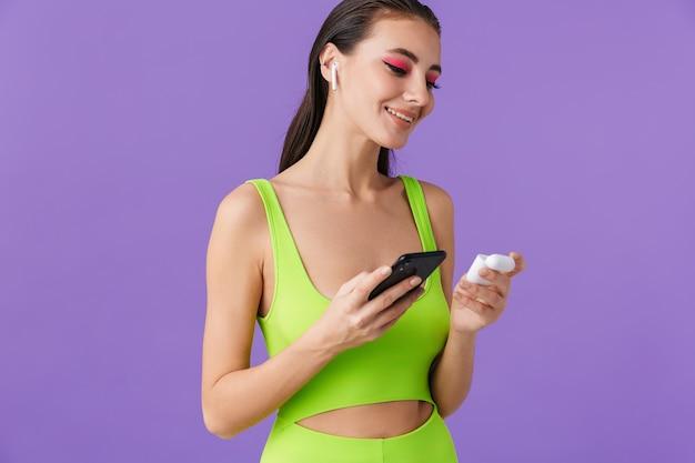Zdjęcie ślicznej uśmiechniętej kobiety z jasnym makijażem za pomocą smartfona i słuchawek