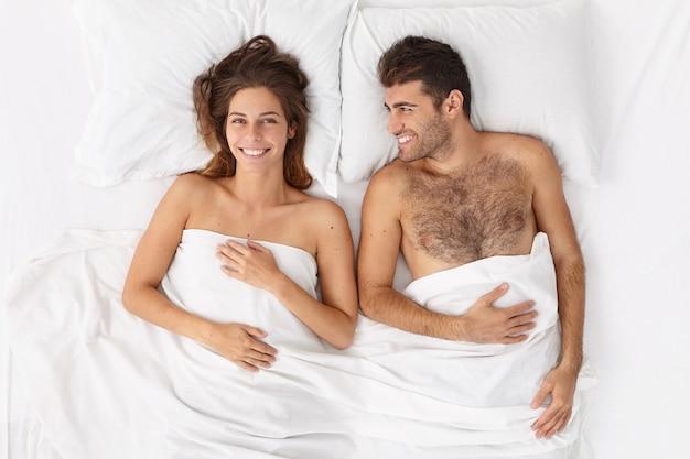 Zdjęcie słodkiego małżeństwa leżącego w łóżku pod białym kocem, radośnie uśmiechającego się, cieszącego się leniwym dniem razem, wypoczętego, przebudzonego po zdrowym śnie. nowożeńcy mają noc poślubną. widok z góry z góry