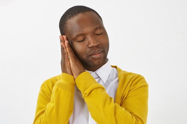 Zdjęcie słodkiego, zmęczonego, młodego afroamerykańskiego mężczyzny z włosiem, kładącego głowę na dłoniach złączonych razem i zamykających oczy, śpiącego spokojnie. śpiący, stylowy ciemnoskóry facet na drzemce