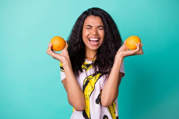 Zdjęcie słodkiej czarnej dziewczyny trzymaj dwie pomarańcze otwarte usta oczy zamknięte nosić bananową koszulkę z nadrukiem na białym tle turkusowy kolor
