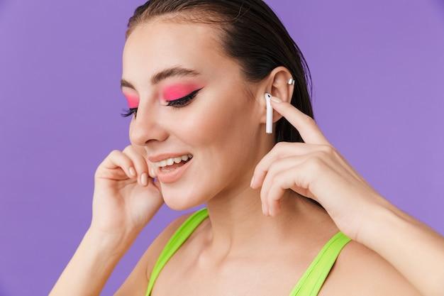 Zdjęcie słodkiej szczęśliwej kobiety z jasnym makijażem za pomocą poduszek do uszu i smling