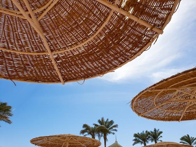 Zdjęcie słomianych parasoli chroniących przed słońcem na plaży przed jasnym błękitnym niebem