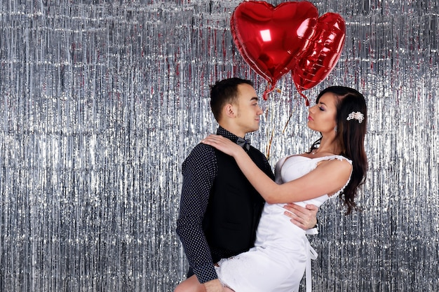 Zdjęcie ślubne. młoda panna młoda i pan młody tańczy na brokatowych zasłonach