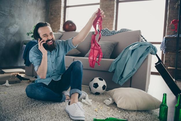 Zdjęcie śmiejącego się hipster faceta trzymającego telefon, opowiadającego przyjaciołom o intymności szczegóły jego aktywnego, niegrzecznego życia noc złego człowieka zegarek czerwony biustonosz ręce siedzące piętro śmieci po imprezie mieszkanie w pomieszczeniu