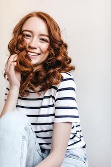 Zdjęcie śmiejącej się dziewczyny jocunda ma na sobie niebieskie dżinsy vintage. urocza ruda kobieta w pasiastej koszulce siedzi w pobliżu białej ściany.