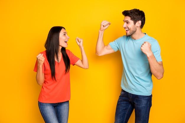 Zdjęcie śmieszne dwie osoby pani facet świętuje zawody sportowe wygrywając mistrzostwa nosić dorywczo niebieskie pomarańczowe koszulki dżinsy izolowane żółty kolor ściany