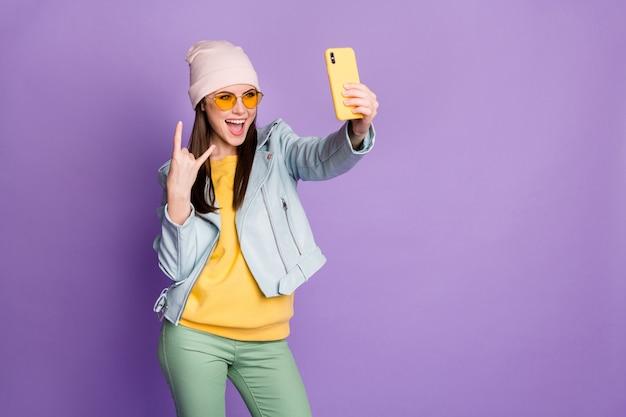 Zdjęcie śmieszne ładne fajne młodzieży pani trzymać telefon zrobić selfie popularny bloger pokazując palec rogi nosić okulary przeciwsłoneczne dorywczo kapelusz kurtka żółty sweter spodnie na białym tle fioletowy kolor tła