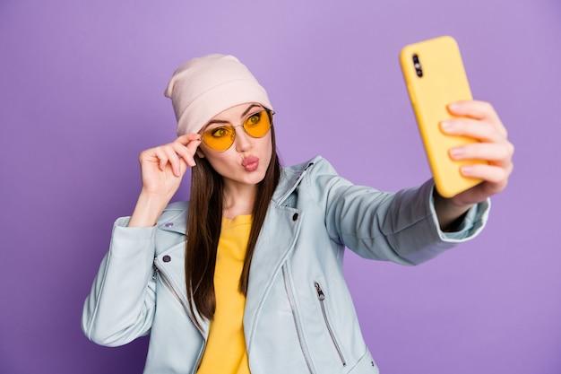 Zdjęcie śmieszne ładne młode pani trzymać telefon zrobić selfie popularne blogger wysyłanie powietrza pocałunki nosić okulary przeciwsłoneczne dorywczo kapelusz kurtka żółty sweter na białym tle fioletowy kolor tła