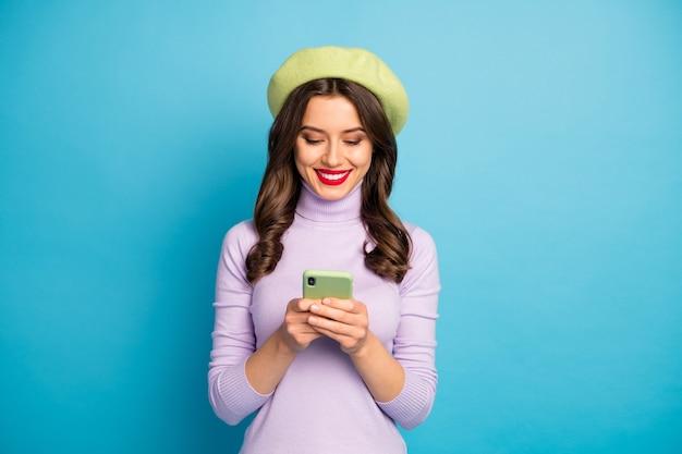 Zdjęcie śmieszne uroczej pani trzymającej telefon za ręce, pisząc wiadomość najlepsi przyjaciele podróżujący nosić fioletowy sweter zielony beret czapka na białym tle niebieski kolor ściany