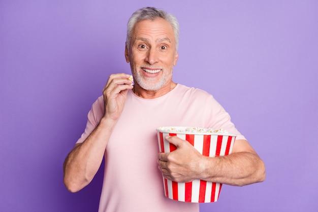 Zdjęcie śmiesznego dziadka przytulać papierowe pudełko jeść popcorn ząbkowany uśmiech nosić różową koszulkę na białym tle fioletowy kolor