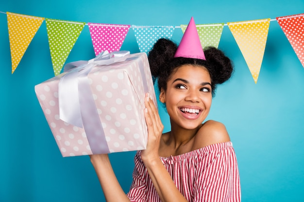 Zdjęcie śmiesznej ciekawej ciemnej skóry pani trzymającej duże pudełko upominkowe urodziny dziewczyny nosić czapkę stożkową czerwoną białą koszulę w paski nagie ramiona kolorowe przerywane flagi wiszą nad niebieską ścianą