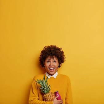 Zdjęcie śmiesznej etnicznej kobiety skoncentrowanej w górę, trzyma świeżego ananasa i smoothie, ma zdrowe odżywianie, ubrane w codzienne ubrania, odizolowane na jasnożółtej ścianie, skopiuj miejsce na tekst
